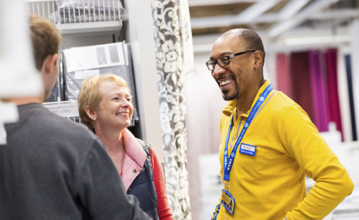 One male IKEA co-worker talking with two customers, one female and one male.