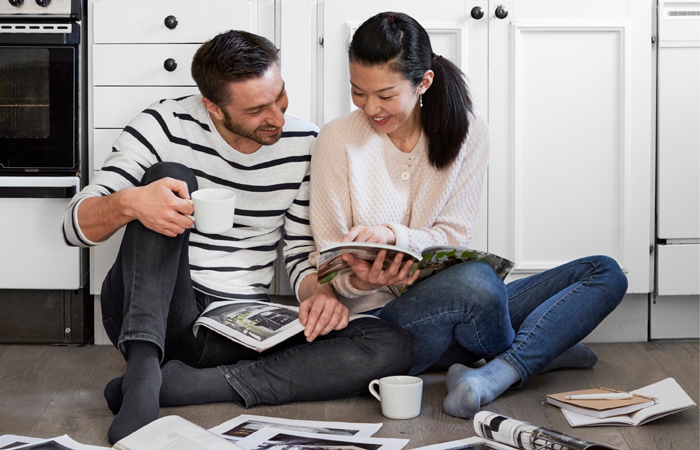 A man and a woman sitting on the floor of a kitchen and checking the IKEA catalogue.