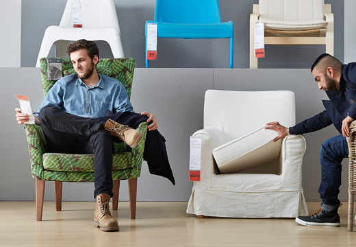 Two men sitting on armchairs in an IKEA store living room area. One is checking the price tag, the other is checking an armchair's pillow.