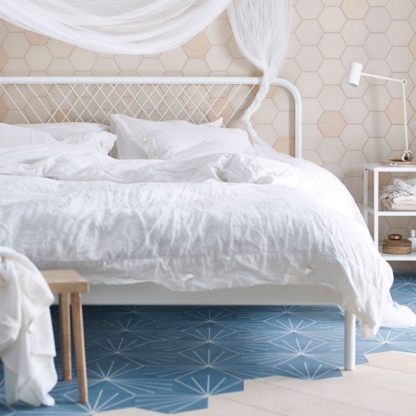 A bed for two in white metal with white bedlinen.