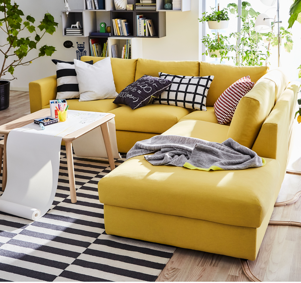Merveilleux Golden Yellow Sectional Sofa With Patterned Cushions In A Bright And Green  Space.
