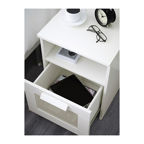 BRIMNES Nightstand IKEA In the drawer there is room for an power strip for your chargers.  You can run the plug to the outlet through the back.