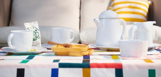 A white tea pot and tea cup set with a honeycomb on an orange dish, and a sofa in the back.