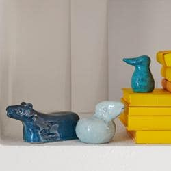 Blue decorative animal statues next to a stack of yellow books.