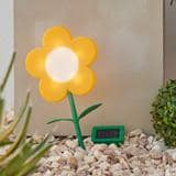 A solar light in the shape of a yellow flower with a green stem standing in a pile of rocks.