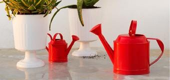 Two red watering cans next to two white vases with greenery sticking out of them.